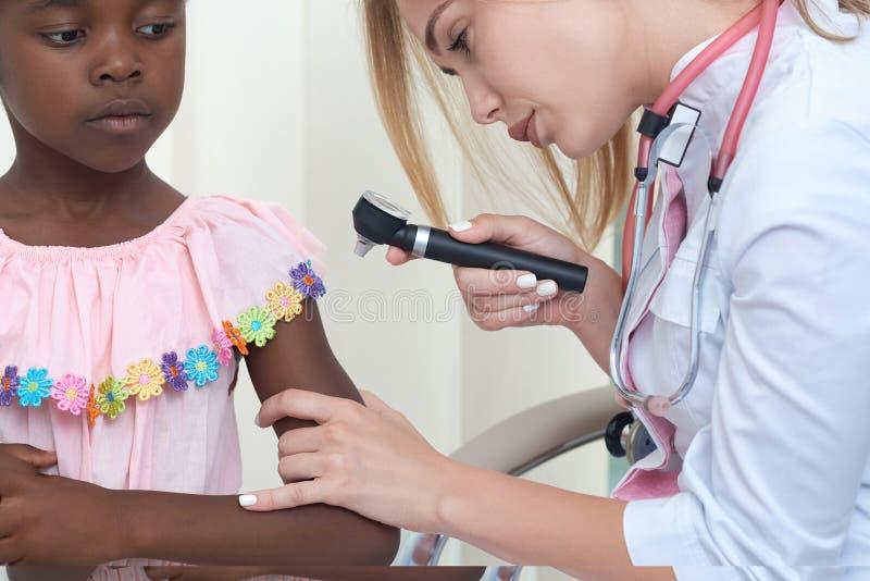 Vrouwelijke arts die huid van kind met dermatoscope onderzoeken stock afbeeldingen