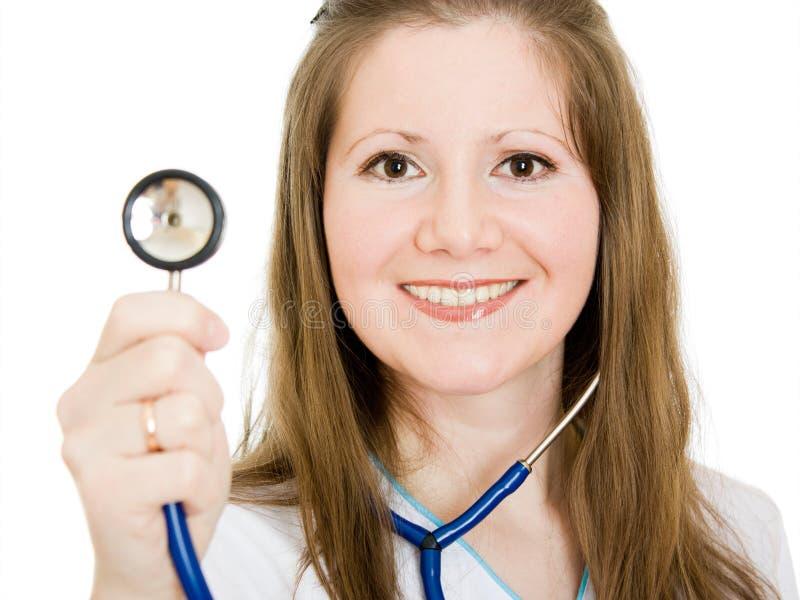 Vrouwelijke arts die met in hand stethoscoop glimlacht royalty-vrije stock afbeeldingen