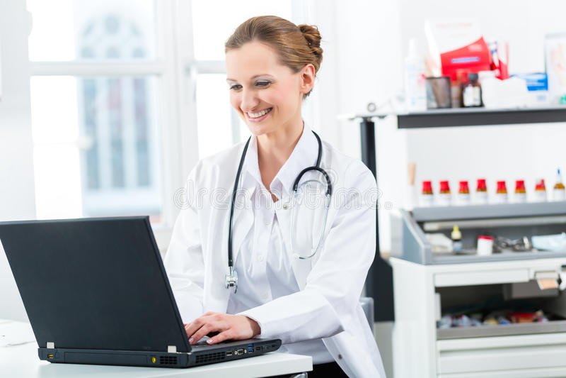 Vrouwelijke arts die op PC in haar kliniek schrijven royalty-vrije stock foto