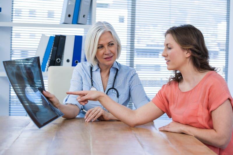 Vrouwelijke arts die x-ray rapport verklaren aan patiënt stock fotografie