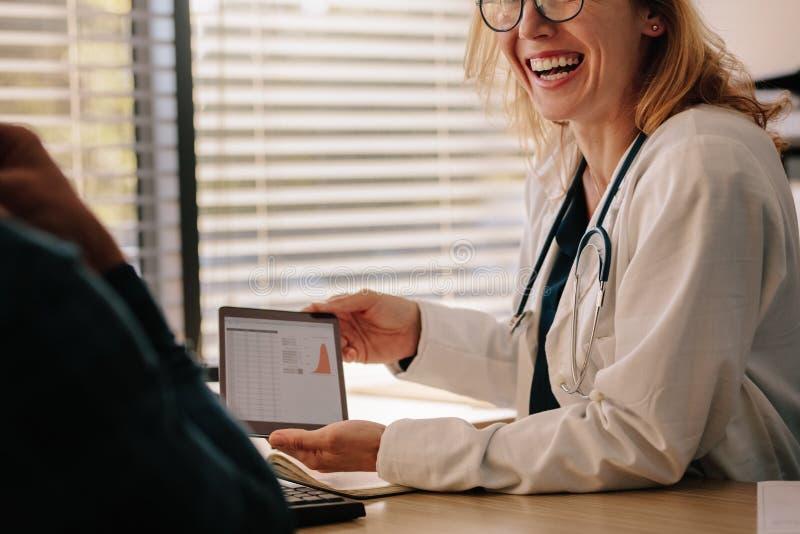 Vrouwelijke arts die testresultaten tonen aan geduldig en glimlachen royalty-vrije stock afbeeldingen