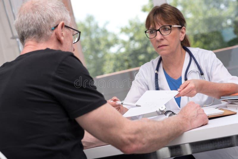 Vrouwelijke arts die voorschrift geven aan haar patiënt stock foto's