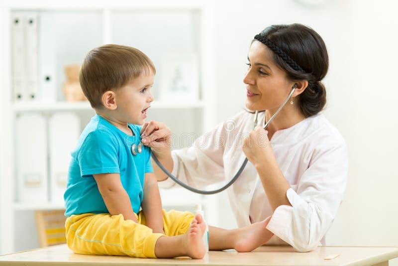 Vrouwelijke arts die weinig kindjongen in het ziekenhuis onderzoeken royalty-vrije stock afbeeldingen