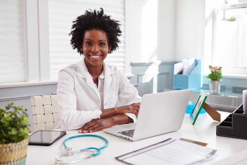 Vrouwelijke arts die in witte laag aan camera in een bureau kijken stock fotografie