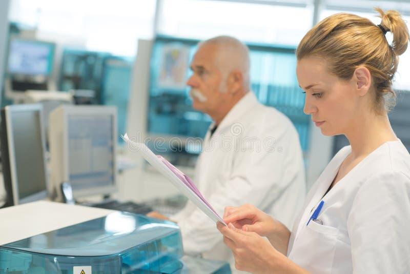 Vrouwelijke arts medisch rapport controleren en collega's die zich erachter bevinden stock foto