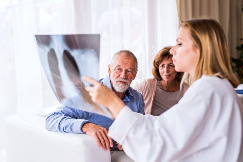 Vrouwelijke arts met het x-ray spreken aan een hoger paar royalty-vrije stock afbeeldingen