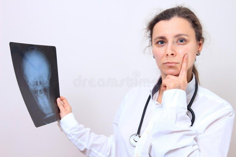 Vrouwelijke arts met x-ray beeld van hoofd Artsengedachten over de resultaten van xray beeld stock fotografie
