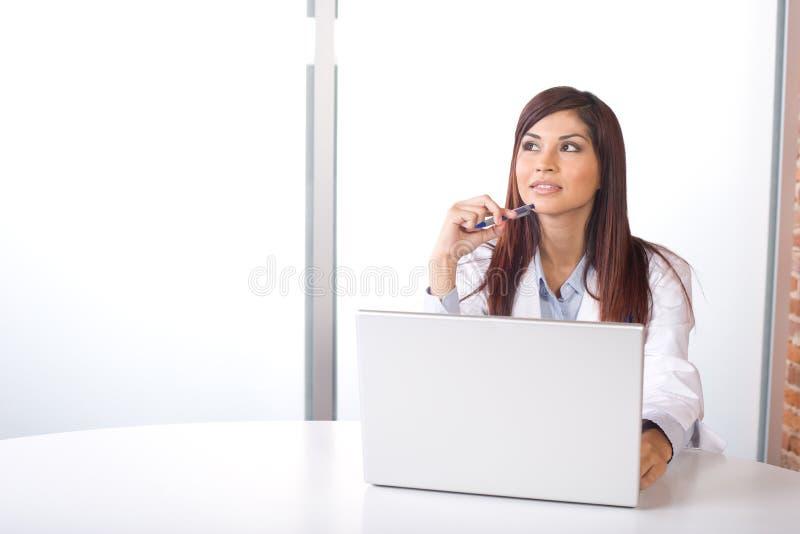 Vrouwelijke arts op computer bij bureau royalty-vrije stock afbeelding