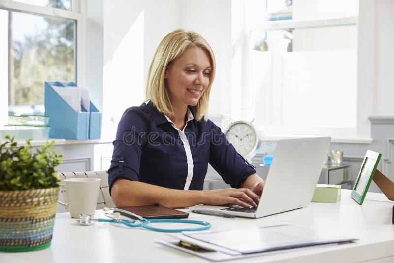 Vrouwelijke Arts Sitting At Desk die bij Laptop in Bureau werken stock afbeeldingen