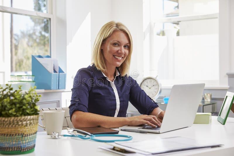 Vrouwelijke Arts Sitting At Desk die bij Laptop in Bureau werken stock afbeelding