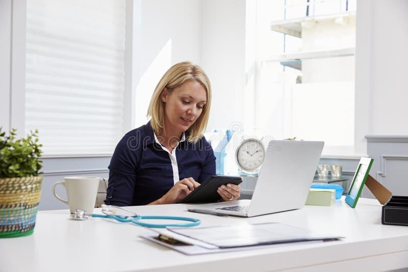 Vrouwelijke Arts Sitting At Desk die Digitale Tablet in Bureau gebruiken stock afbeelding
