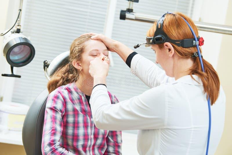 Vrouwelijke arts van ENT keel van de oorneus op het werk die meisjesneus onderzoeken stock afbeelding