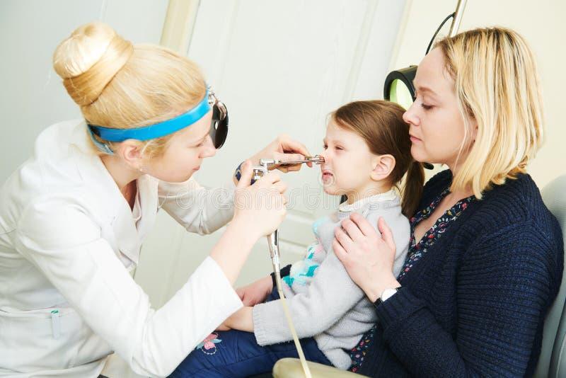 Vrouwelijke arts van ENT keel van de oorneus op het werk die meisjesneus onderzoeken stock fotografie