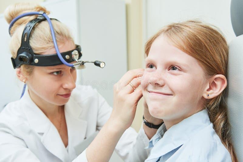 Vrouwelijke arts van ENT keel van de oorneus op het werk die meisjesoor onderzoeken royalty-vrije stock afbeelding