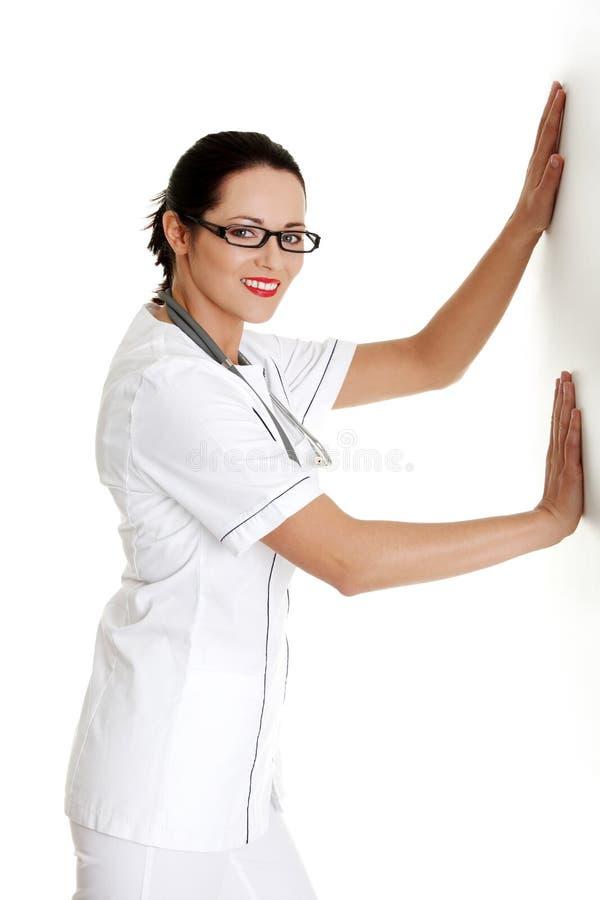 Vrouwelijke arts of verpleegster die of op muur duwen leunen stock afbeeldingen