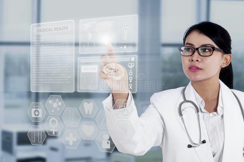 Vrouwelijke arts wat betreft medische interface stock afbeeldingen