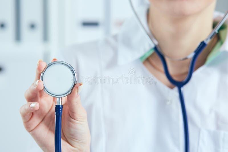 Vrouwelijke artsenhand die stethoscoop voor controle tonen Arts met stethoscoop in hand op het ziekenhuisachtergrond voor medisch royalty-vrije stock foto