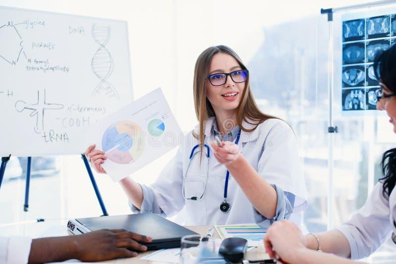 Vrouwelijke artsenholding in handen x ray resultaat op de vergadering bij moderne kliniek Professionele artsen van multi etnische royalty-vrije stock fotografie