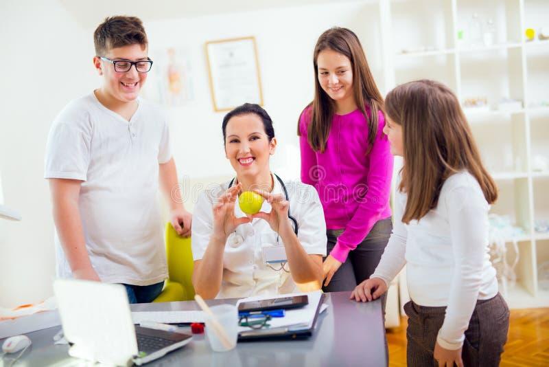 Vrouwelijke artsenvoedingsdeskundige en geduldige tieners Arts die een appel houdt stock afbeeldingen