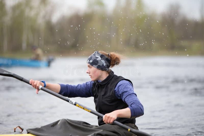 Vrouwelijke atleet belast met het roeien Meisje in een sportenboot met roeispanen stock fotografie