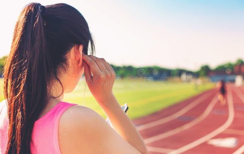 Vrouwelijke atleet die aan muziek op een renbaan luisteren stock foto's