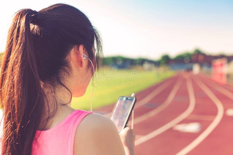 Vrouwelijke atleet die aan muziek op een renbaan luisteren royalty-vrije stock foto