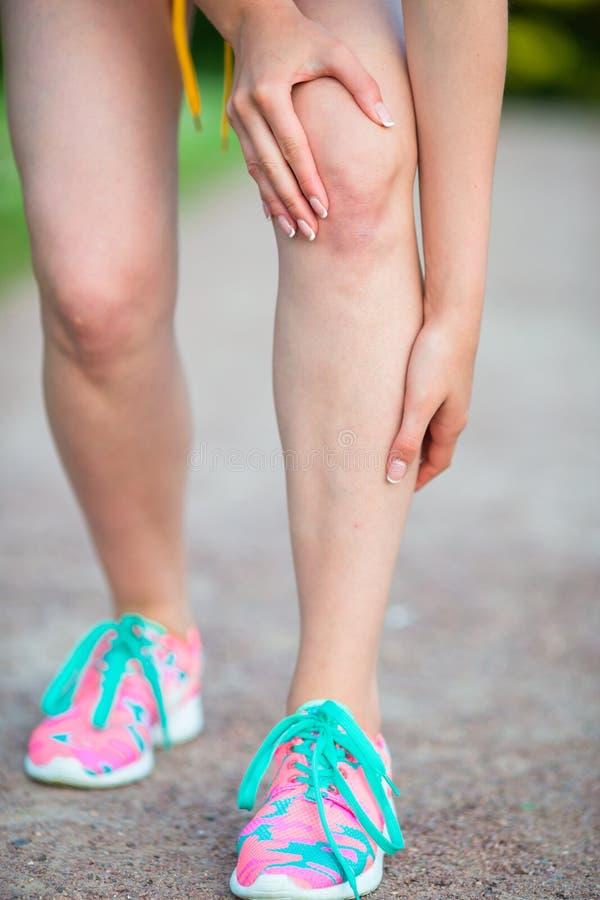 Vrouwelijke atleet die aan pijn in been lijden terwijl in openlucht het uitoefenen Agentverwonding die - kniepijn kwetsen royalty-vrije stock afbeeldingen
