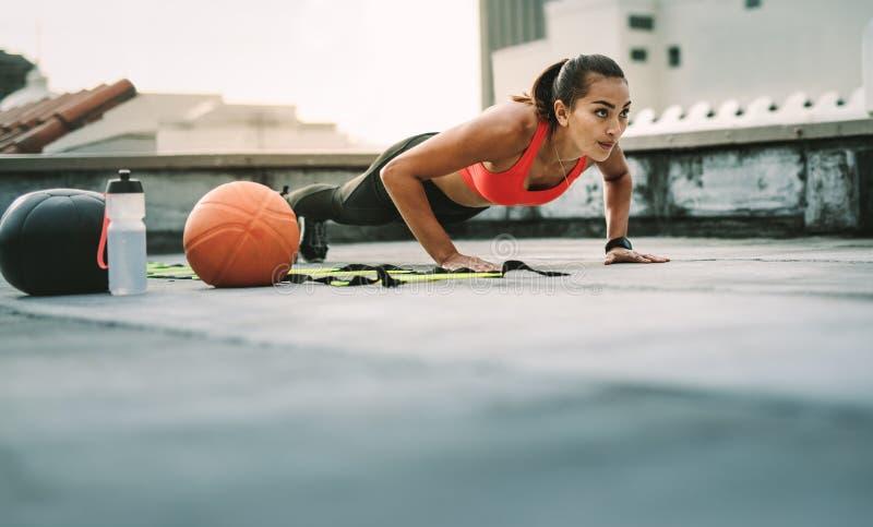 Vrouwelijke atleet die geschiktheidstraining op dak doen royalty-vrije stock foto