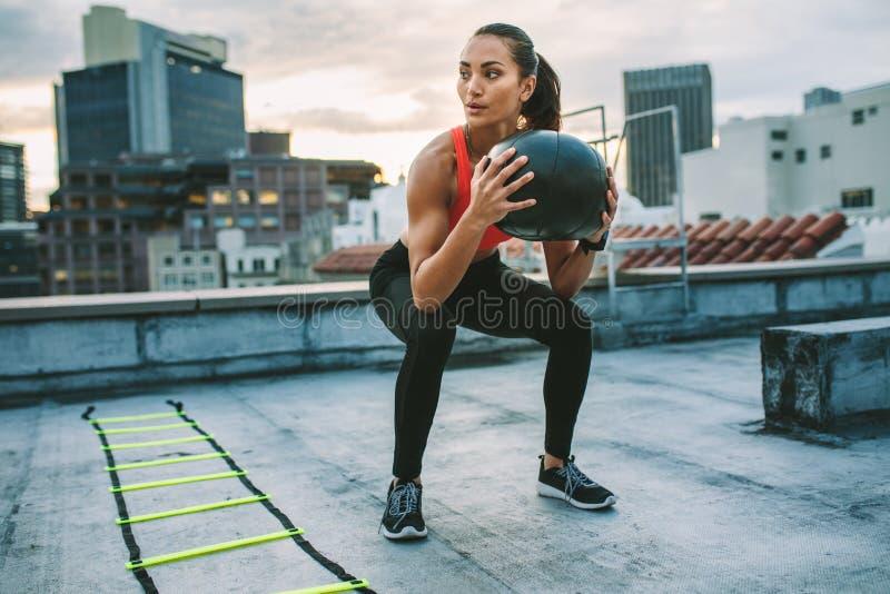 Vrouwelijke atleet die hurkzit doen die een geneeskundebal houden royalty-vrije stock foto