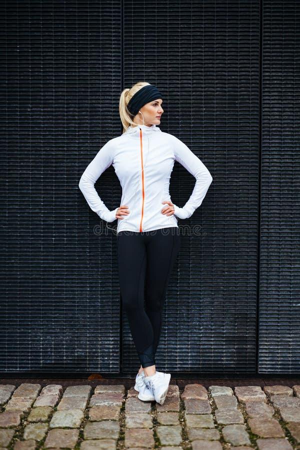 Vrouwelijke atleet die na jogging in de stad rusten stock fotografie