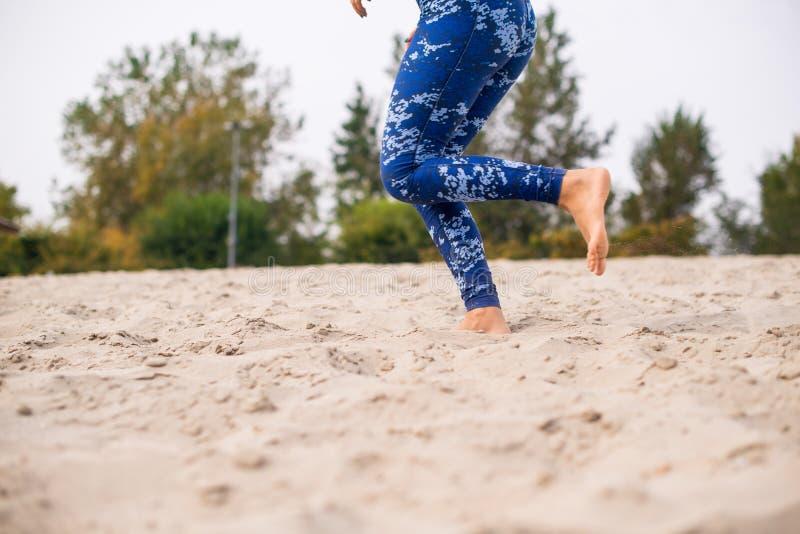 Vrouwelijke atleet die op het strand, lage sectie lopen stock foto