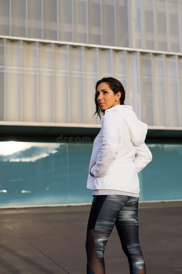 Vrouwelijke atleet die over schouder kijken stock afbeelding