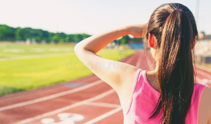 Vrouwelijke atleet die uit een renbaan bekijken stock foto