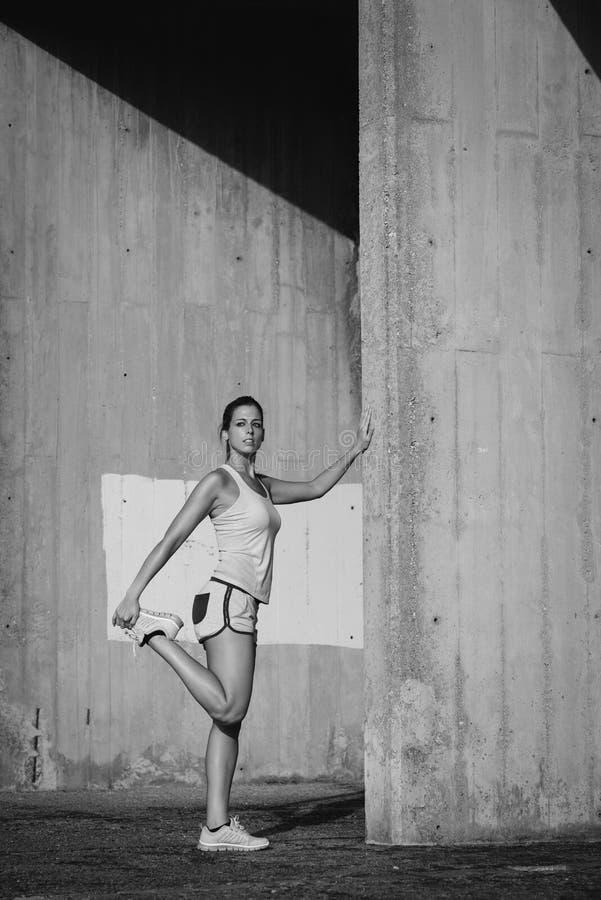 Vrouwelijke atleet het uitrekken zich benen voor het lopen royalty-vrije stock afbeelding