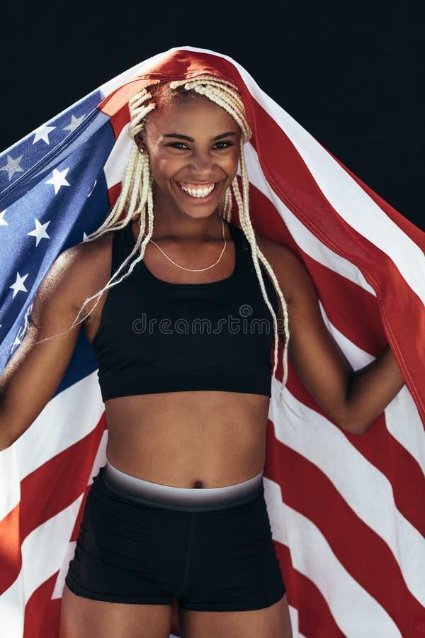 Vrouwelijke atleet het vieren overwinning die Amerikaanse vlag houden stock foto's