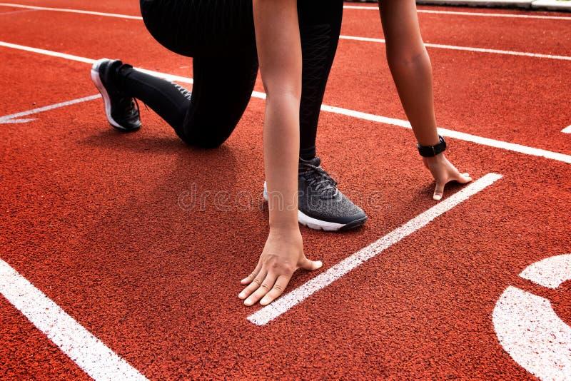 Vrouwelijke atleet op de beginlijn van spoor het voorbereidingen treffen royalty-vrije stock fotografie