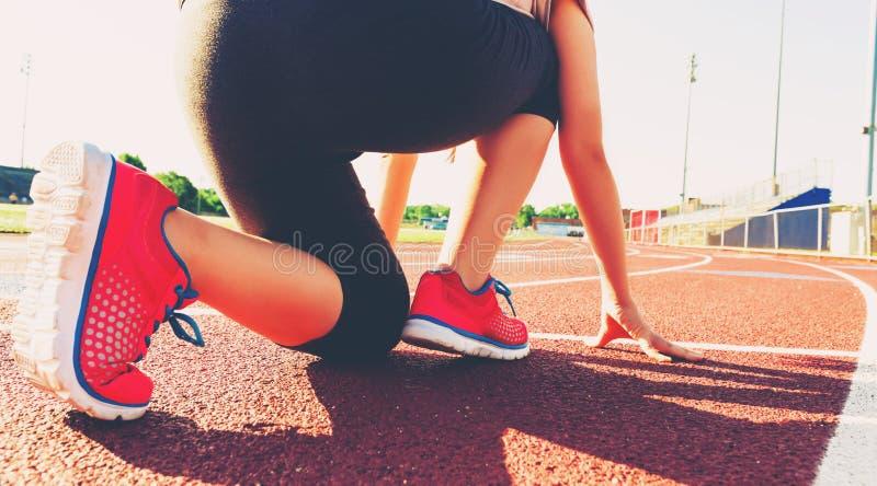 Vrouwelijke atleet op de beginnende lijn van een stadionspoor stock afbeelding