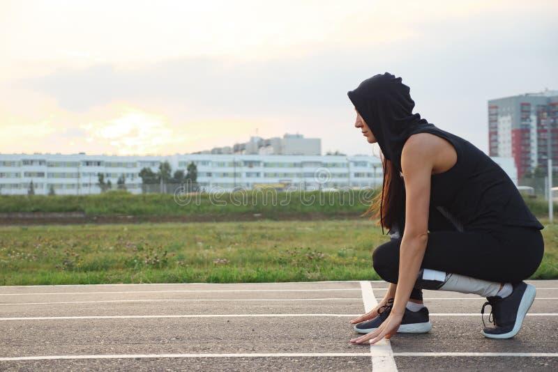 Vrouwelijke atleet op de beginnende lijn van een stadionspoor die voor een looppas voorbereidingen treffen royalty-vrije stock afbeelding