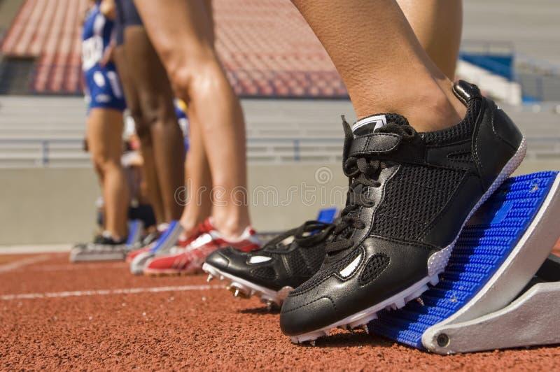 Vrouwelijke Atleet On Starting Blocks stock foto's