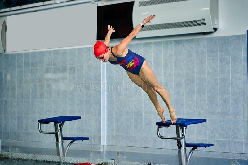 Vrouwelijke atletensprongen aan het poolwater Vrouw op middelbare leeftijd professioneel belast met het zwemmen royalty-vrije stock foto's