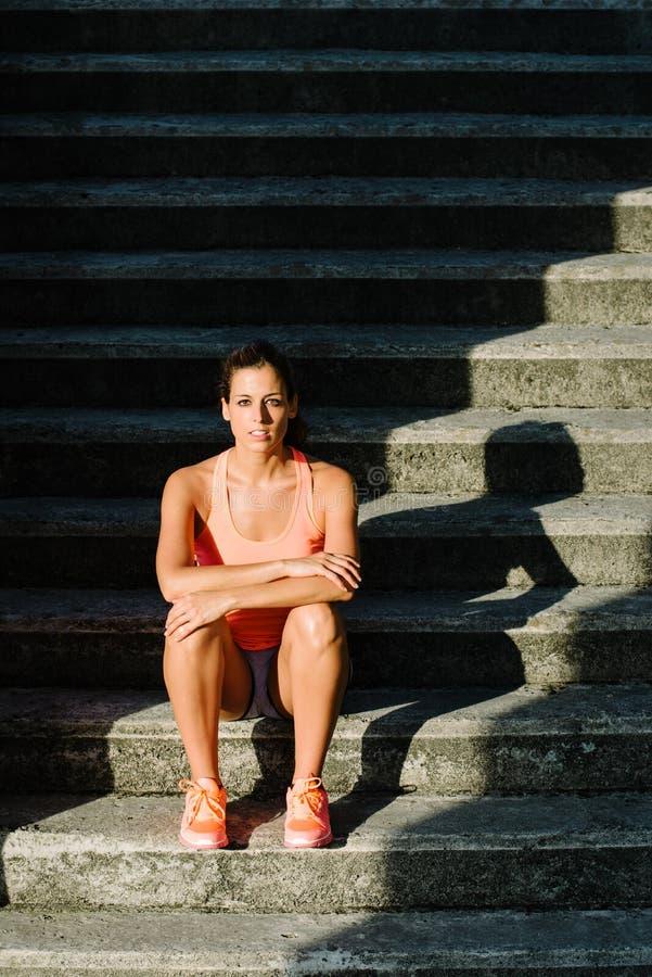 Vrouwelijke atletenzitting op treden en het bekijken camera royalty-vrije stock afbeelding