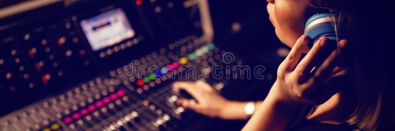Vrouwelijke audioingenieur die aan hoofdtelefoons luisteren stock foto's