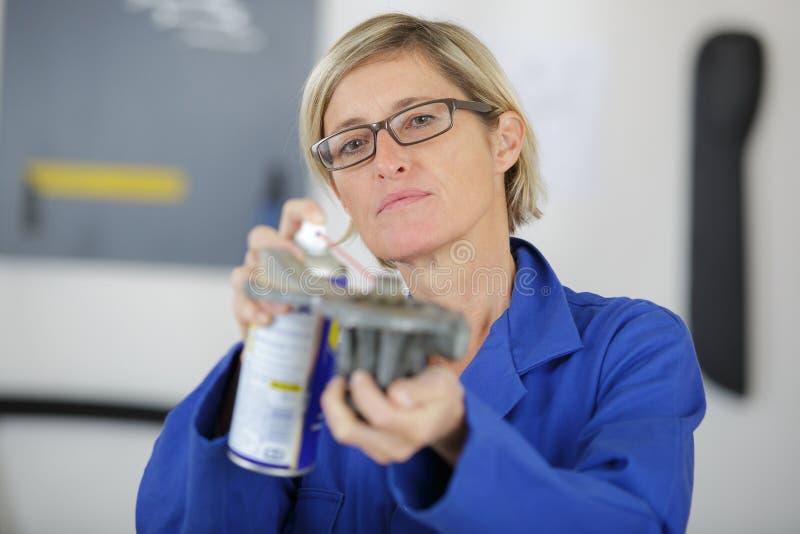 Vrouwelijke autowerktuigkundige in garage met oude motor van een autozuiger stock foto's