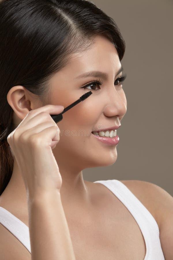 Vrouwelijke Aziaat die mascara toepassen stock fotografie