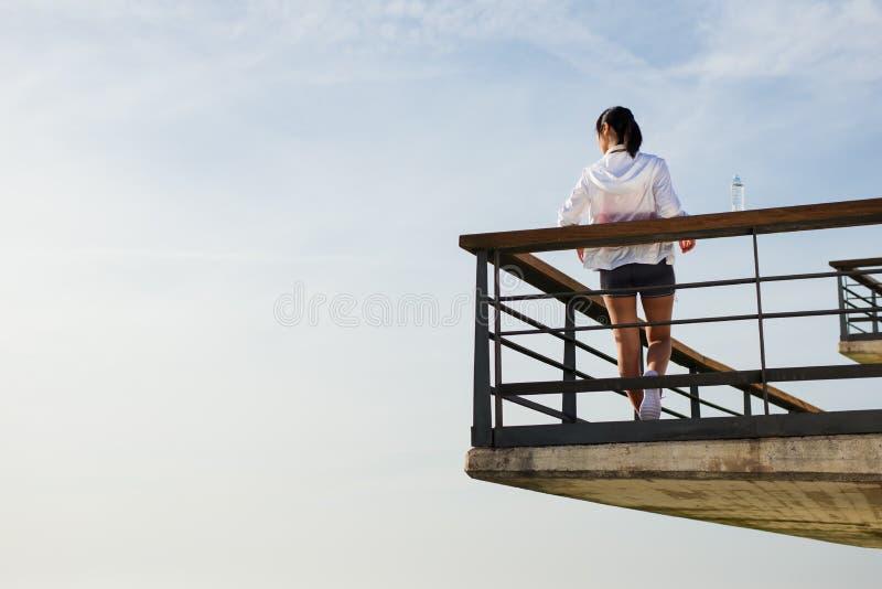 Vrouwelijke Aziatische atleet die na stedelijke training rusten royalty-vrije stock foto