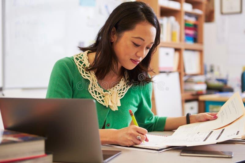 Vrouwelijke Aziatische leraar die bij haar bureau studentsï het werk ¿ merken ½ stock foto's