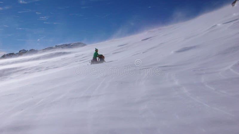 Vrouwelijke backcountry skiër die in een onweer in de Zwitserse Alpen knielen stock afbeeldingen
