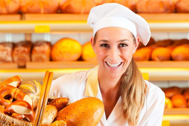 Vrouwelijke bakker in bakkerij verkopend brood door mand stock foto's