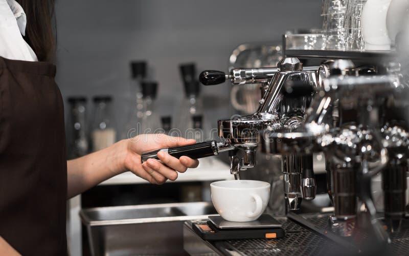Vrouwelijke barista Cafe gebruikend koffie-makende machine die koffie PR maken stock foto's