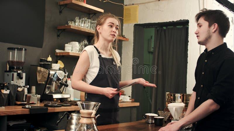 Vrouwelijke barista die aan klant in een koffie spreken, die orde nemen royalty-vrije stock afbeelding